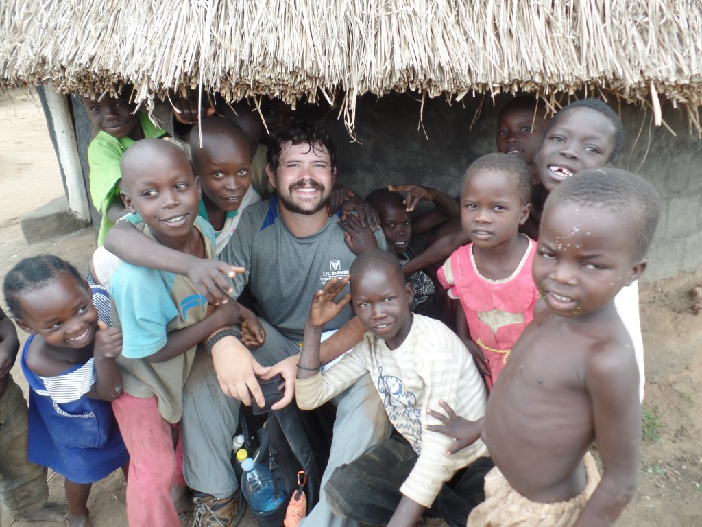 Cody Blumenshine surrounded by village kids in Uganda.